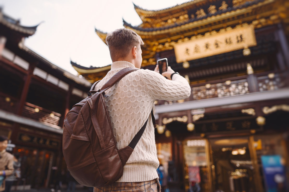 male tourist taking photos of a pagoda at Yuyuan market in Shanghai during his visit to China